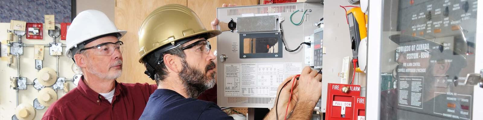 Apprentice electrician being mentored by a journeyman electrician