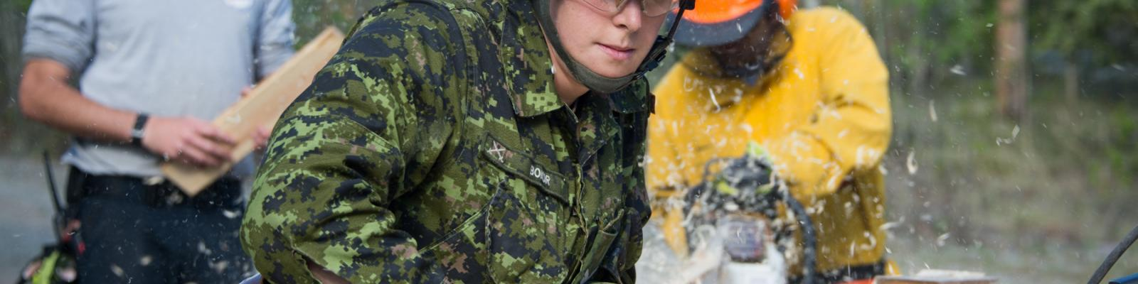 Corporal Laura Bokor steadies a board while participating in structural field training during Operation NANOOK-TATIGIIT 19 in Whitehorse, Yukon, May 28, 2019.